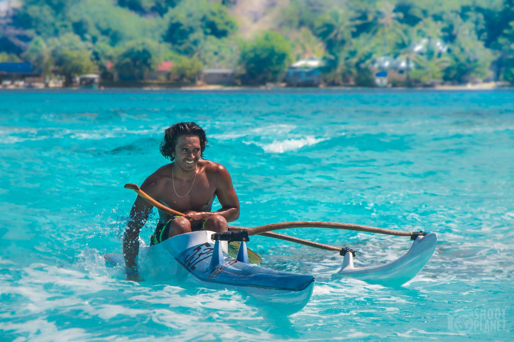 Tahitian man canoeing on Bora Bora lagoon